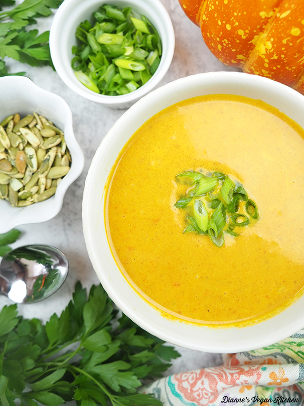 bowl of pumpkin ginger soup with pumpkin seeds and scallions