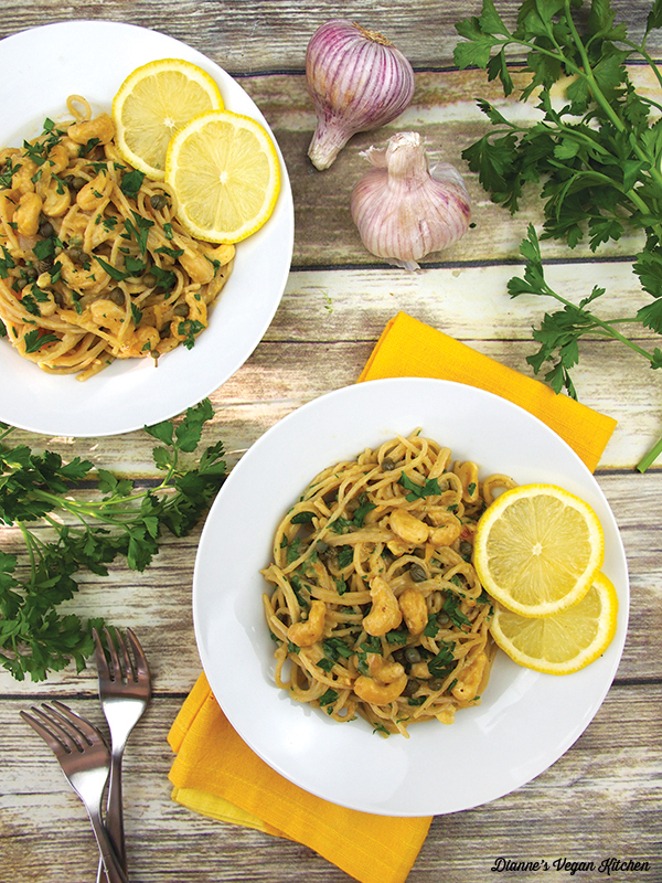 two plates of pasta overhead with parsley and garlic