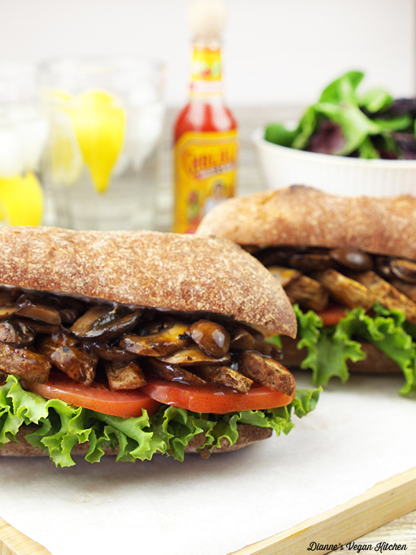 2 po' boy sandwiches with salad and lemon water
