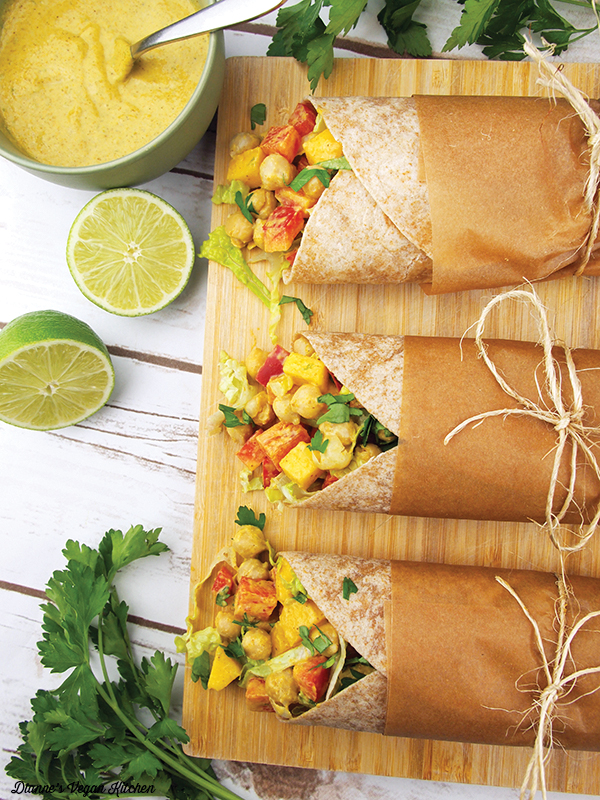 Curried Mango Chickpea Wraps from The Plant-Based Diet Meal Plan by Heather Nicholas on cutting board with bowl of tahini dressing, limes, and cilantro sprigs