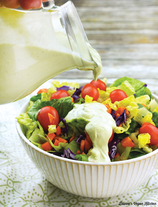 pouring ranch dressing on a salad