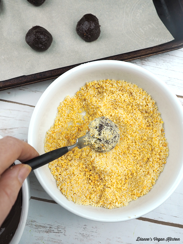 dipping chocolate ball into crushed peanuts