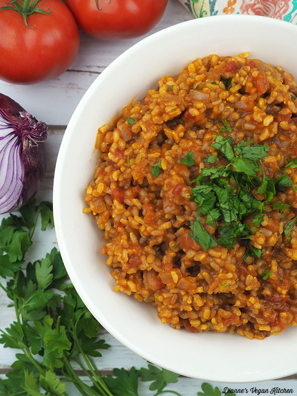Vegan Spanish Rice in bowl overhead with tomatoes and onion