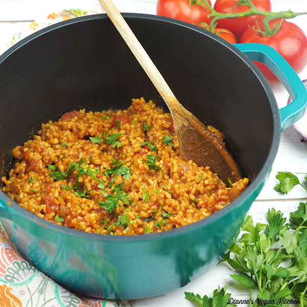 Cooked Vegan Spanish Rice in pot with wooden spoon