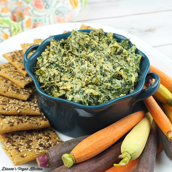 spinach artichoke dip in bowl with carrots and crackers square