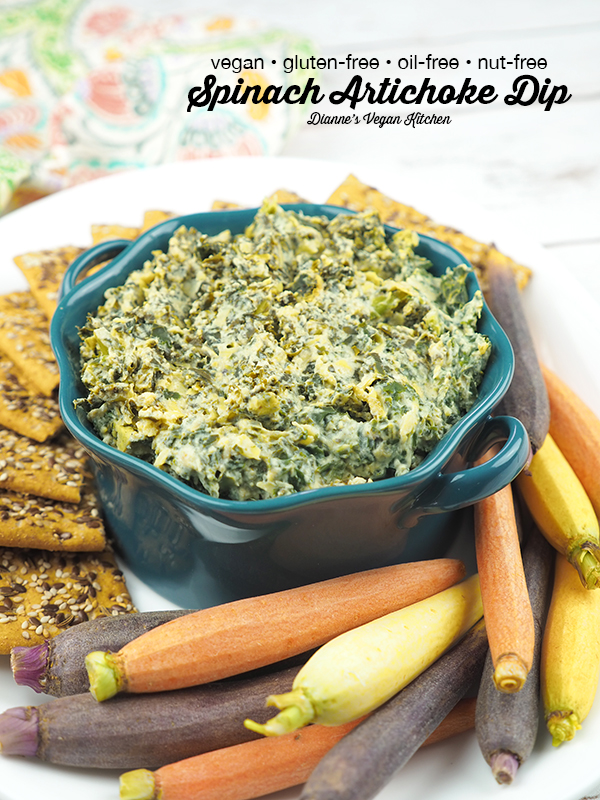 spinach artichoke dip in bowl with carrots and crackers with text overlay
