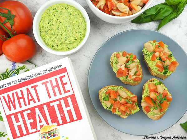 Pesto White Bean Bruschetta on plate with What the Health book