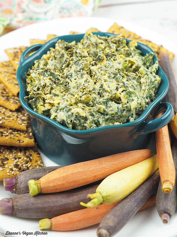 Vegan Spinach Artichoke Dip vertical with crackers and carrots
