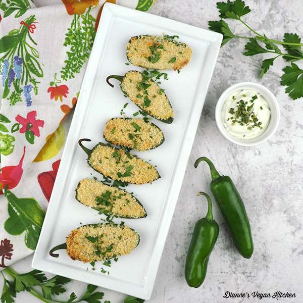 Vegan Jalapeno Poppers on serving tray with extra peppers and cheese