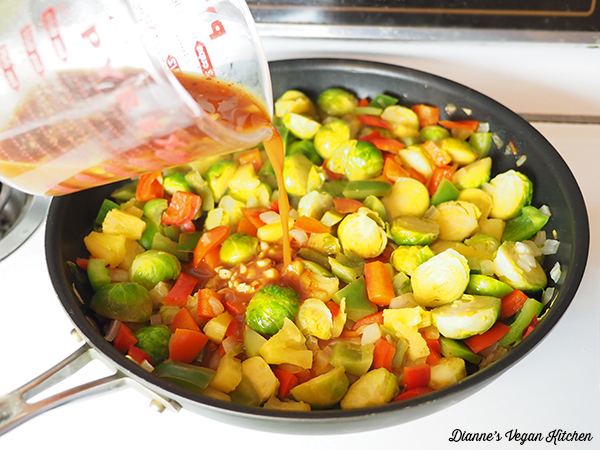 pouring sweet and sour sauce over vegetables