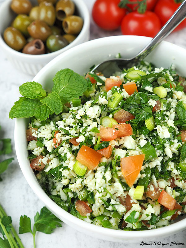 cauliflower tabbouleh with spoon, olives, and tomatos