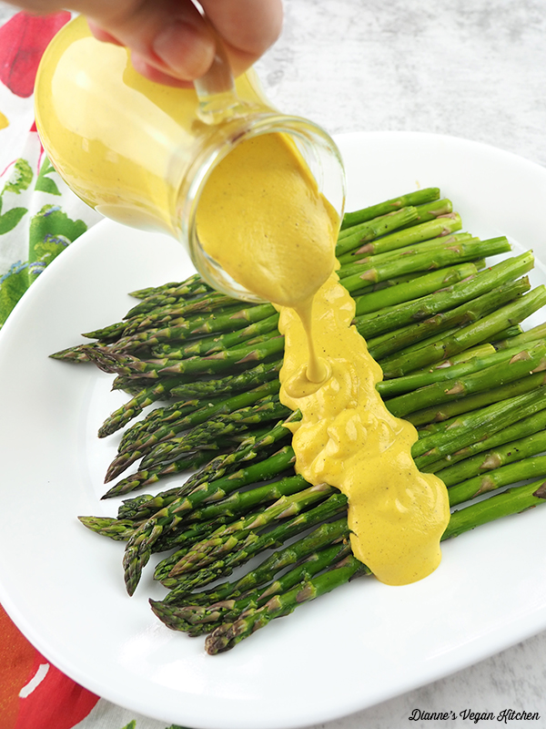 Pouring Vegan Hollandaise Sauce over asparagus