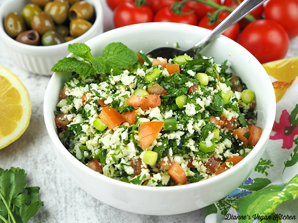 tabbouleh in bowl with tomatoes and olives horizontal