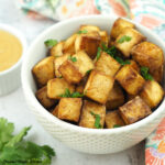 baked tofu in bowl with peanut dipping sauce square