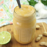 spicy peanut sauce in jar with spoon, lime, and peanuts