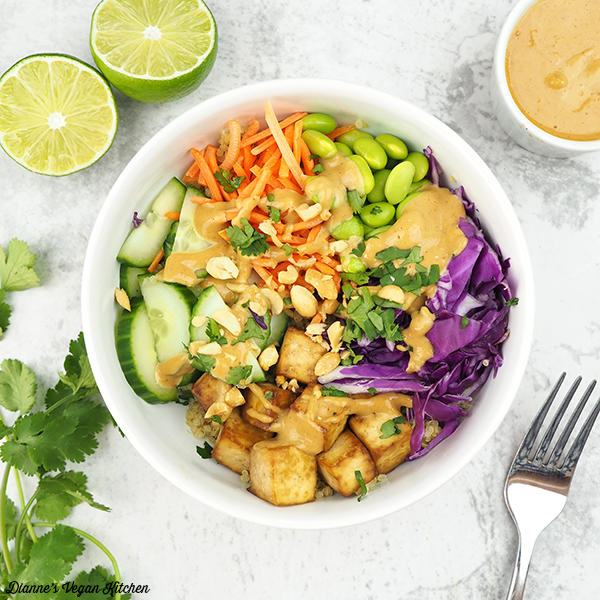 quinoa salad in bowl from above with peanut sauce and limes