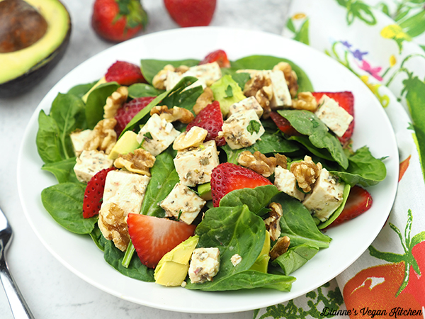 spinach salad in bowl with avocado and strawberries horizontal