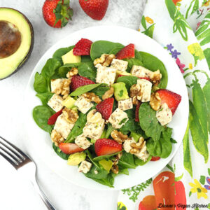 spinach salad in bowl overhead with strawberries and avocado square