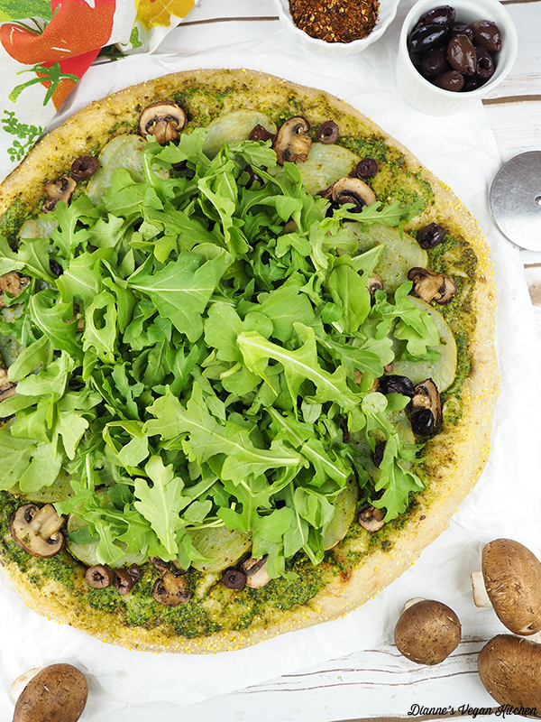 pizza with mushrooms, pizza slicer, and olives
