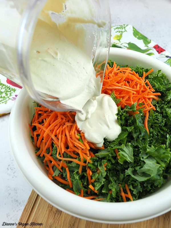 pouring dressing over kale and carrots