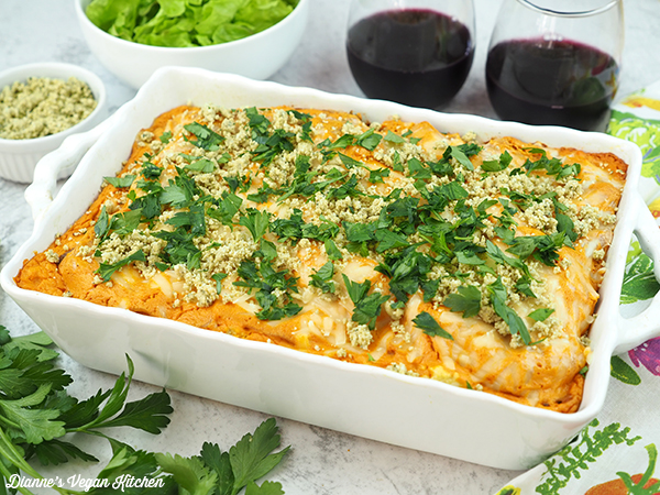 Buffalo Chicken Lasagna in baking dish with glasses of wine and salad horizontal