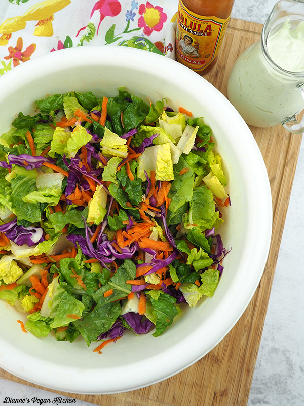 Salad in mixing bowl with ranch dressing