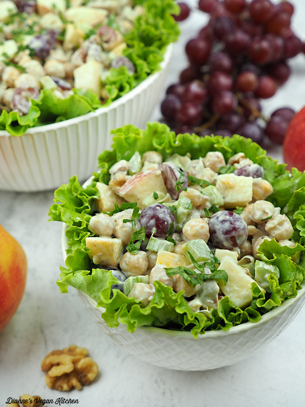 Vegan Chickpea Waldorf Salad in small bowl with grapes and larger bowl in the background