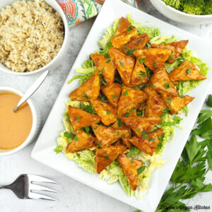 Peanut Satay Tofu Triangles on platter with peanut sauce, brown rice, and broccoli