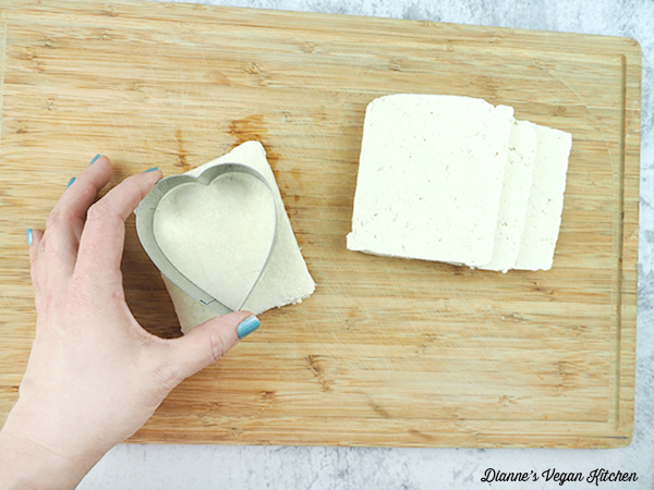 cutting a heart out of tofu with cookie cutter