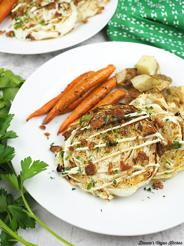 cabbage steaks on plate with potatoes and carrots