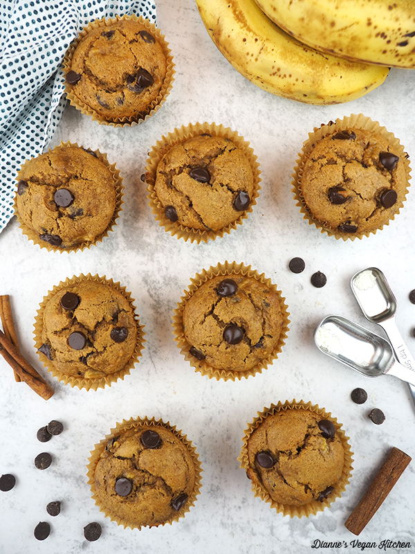 muffins overhead with bananas, spoons, chocolate chips, and cinnamon sticks