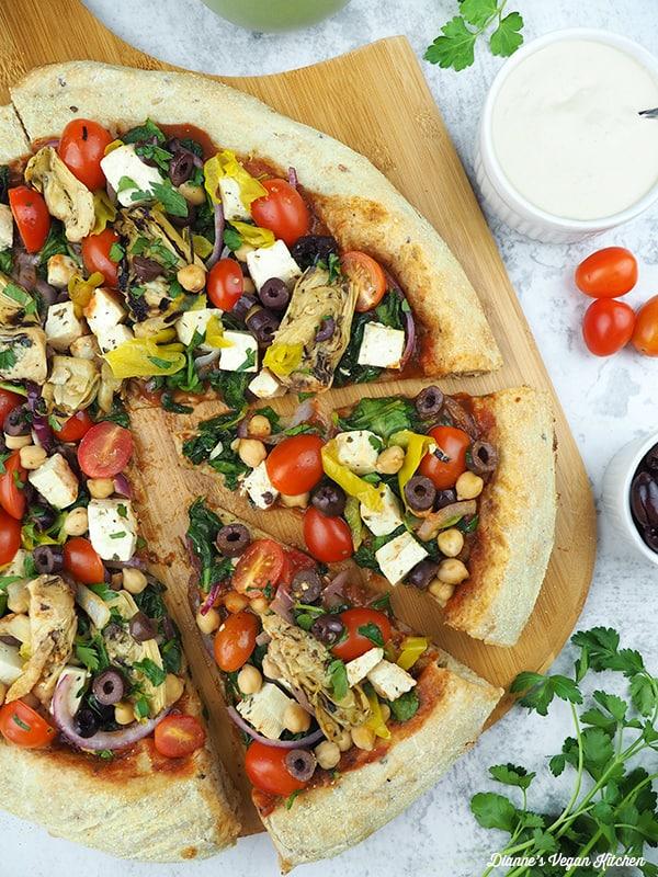 vegan greek pizza on pizza paddle