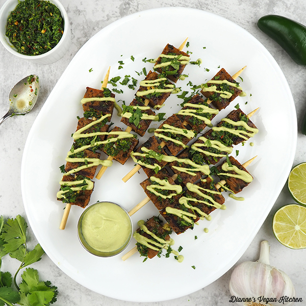Seitan Skewers on platter with chimichurri, limes, jalapeño