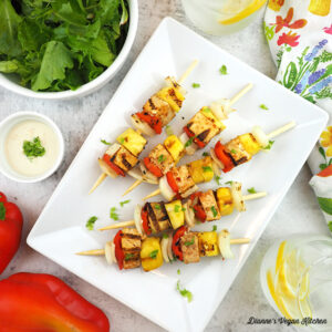 Skewers on plate with peppers and a salad