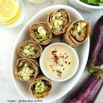 eggplant wraps in dish with tahini dressing and text overlay