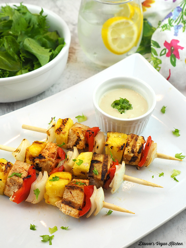 Grilled Tofu Skewers on a plate with salad and water