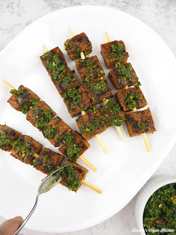 spooning chimichurri onto skewers