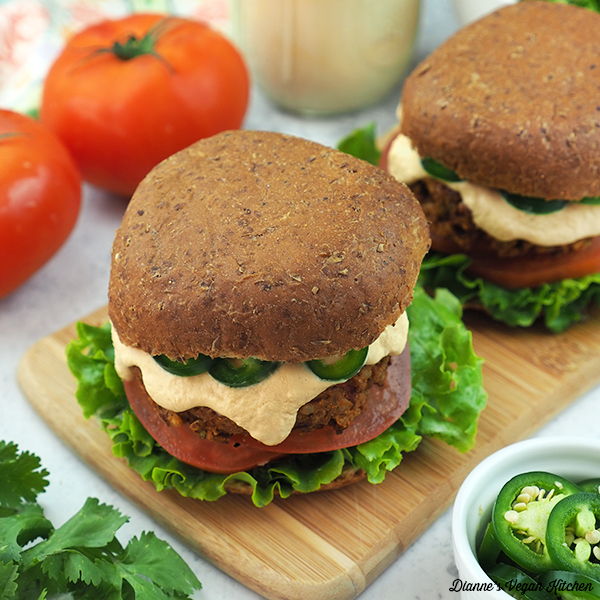 two Chipotle Lentil Burgers with tomatoes and jar of cheese