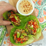 Vegan Lettuce Wraps on cutting board with my hand with text overlay