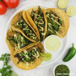 Seitan Chimichurri Tacos on plate with tomatoes, limes, and peppers