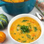 bowl of pumpkin curry with pot in background with text overlay