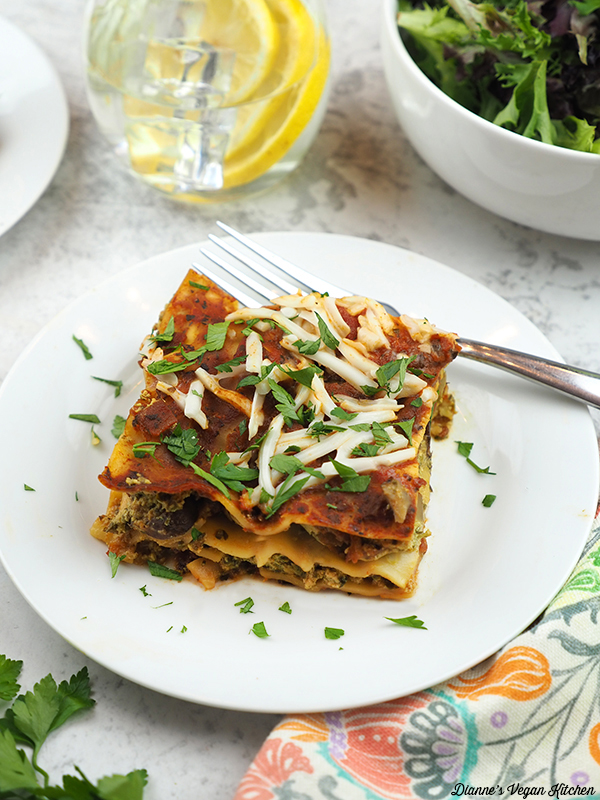 slice of lasagna with lemon water and salad