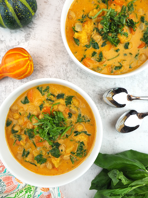 two bowls of pumpkin curry overhead with spoons and pumpkins
