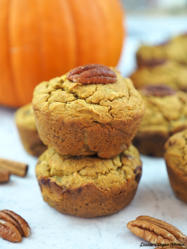two muffins stacked with pumpkin in background