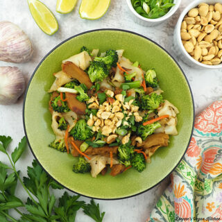 bowl of Vegan Pad See Ew noodles with limes, garlic, peanuts, scallions, and parsley