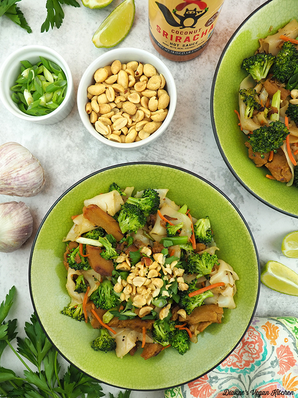 two bowls of Vegan Pad See Ew with peanuts, scallions, limes, hot sauce, and garlic
