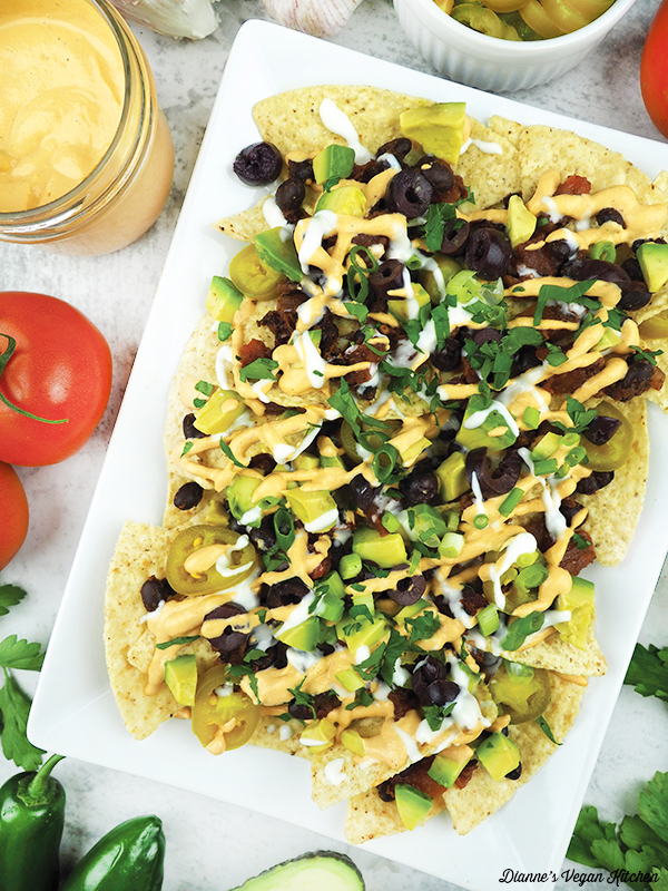 vegan nachos with cheese sauce and tomatoes