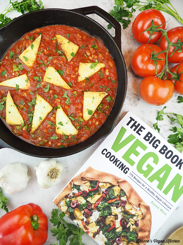 Pan with The Big Book of Vegan Cooking, tomatoes, parsley, garlic, and a pepper