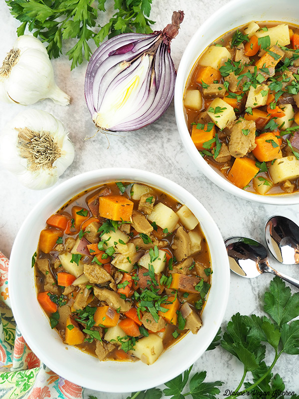 two bowls of stew with garlic, onion, and parsley