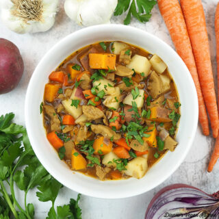 of Seitan Stew overhead with carrots, onion, garlic, potatoes, and parsley, square